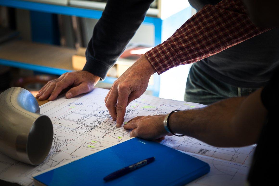 Mani di ingegneri su progetto. Main Workshop