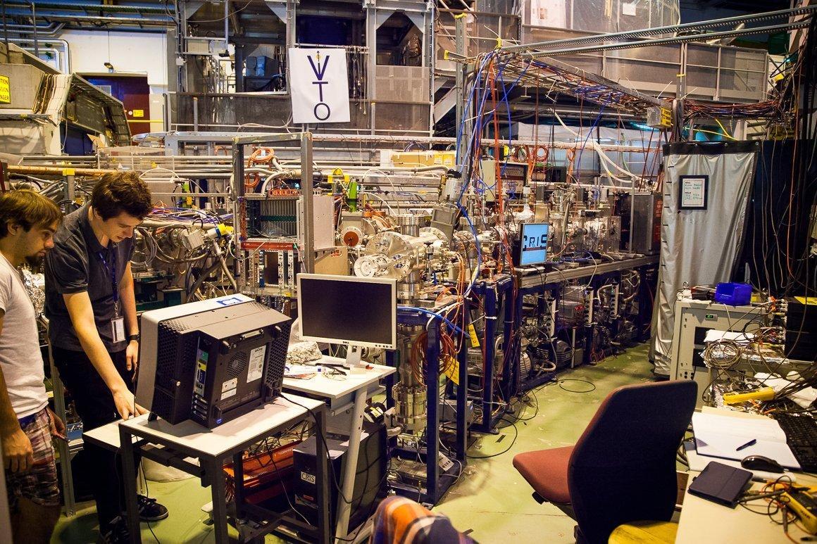Due scienziati lavorano tra cavi e computer all'interno di ISOLDE